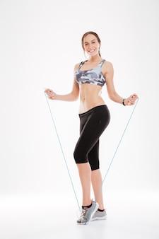Mooie fitness vrouw van de volledige lengte met springtouw in studio. . geïsoleerd