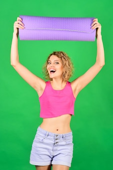 Mooie fitnessinstructeur met gymmat sportvrouw houdt opgerolde oefenmat gezondheidsfitness vast