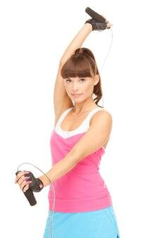Mooie fitnessinstructeur met springtouw over wit