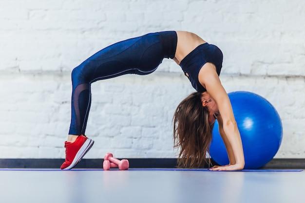 Mooie fitnessvrouw die met blauwe bal in gymnastiek uitoefent