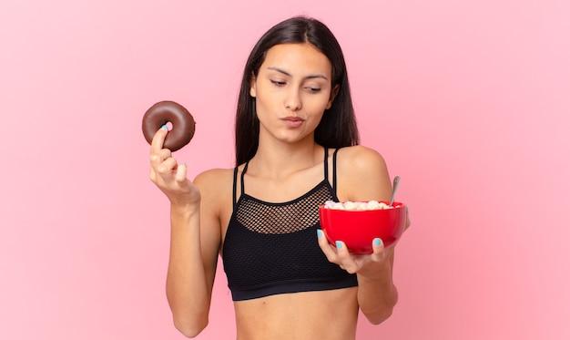 Mooie fitnessvrouw met een donut en een ontbijtkom