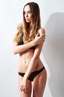 Mooie, fitte en sportieve vrouw in een zwembroek. vetverlies, liposuctie en cellulitisverwijderingsconcept.