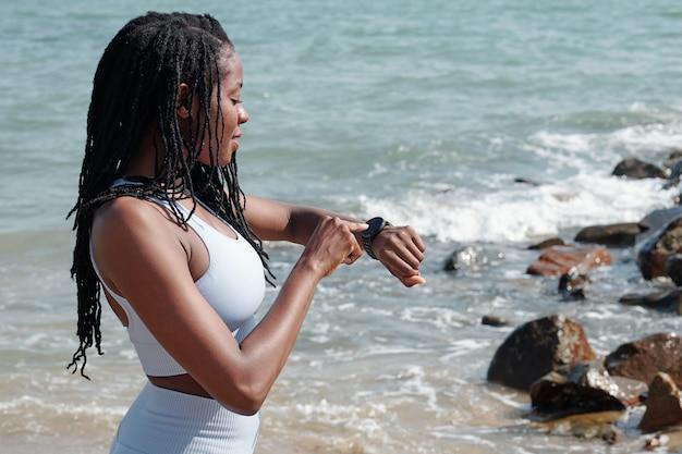 Mooie fitte jonge sportvrouw die op het strand staat en fitnesstracker controleert op haar slimme horloge