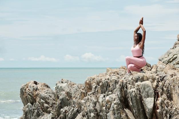 Mooie fitte jonge vrouw die 's ochtends geniet van sporten op rotsachtig strand