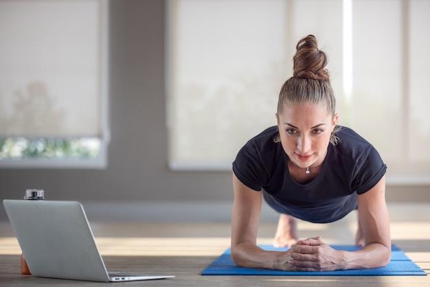 Mooie fitte vrouw die yogaplank doet en online tutorials bekijkt op haar laptop