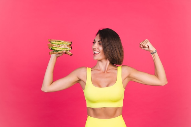 Mooie fitte vrouw in gele, goed passende sportkleding op roze muur, blij met gezonde avocado-sandwich
