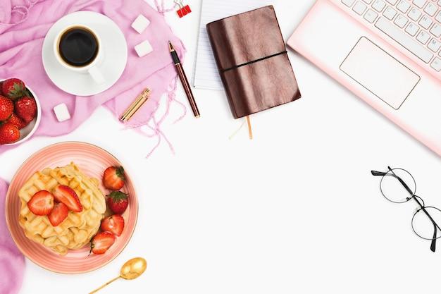 Mooie flatlay arrangement met kopje koffie, warme wafels met room en aardbeien, laptop en andere zakelijke accessoires: concept van drukke ochtendontbijt, witte achtergrond.