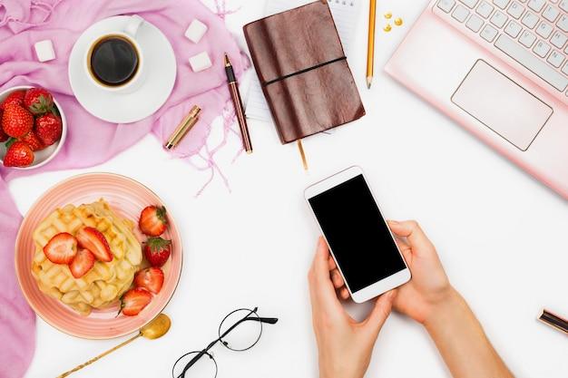 Mooie flatlay-regeling met kop koffie, hete wafels met room en aardbeien, laptop en de holdingssmartphone van de vrouwenhand: concept bezig ochtendontbijt, witte achtergrond.