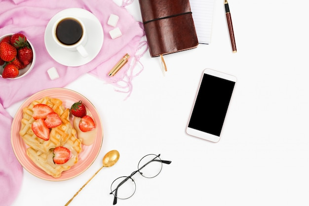 Mooie flatlay regeling met kopje koffie, warme wafels met slagroom, smartphone met zwarte copyspace en andere zakelijke accessoires: concept van drukke ochtendontbijt, witte achtergrond.
