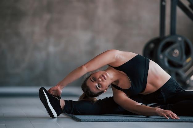 Mooie flexibiliteit. prachtige blonde vrouw in de sportschool in haar weekend.