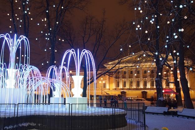 Mooie fontein met avondverlichting in de winter in de stad.