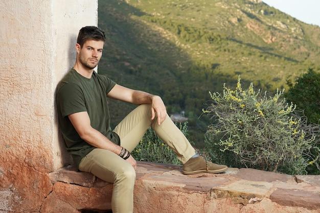 Mooie foto van een charmante man die tegen de muur zit en leunt met uitzicht op de natuur erachter