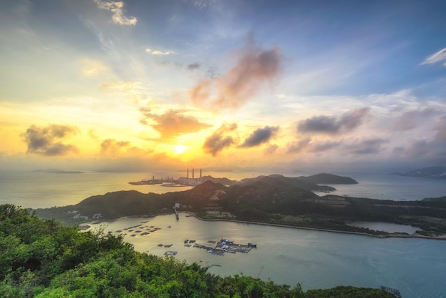 Mooie foto van een eiland omringd door zee onder een bewolkte hemel bij zonsondergang