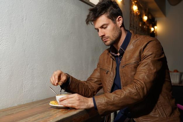 Mooie foto van een elegante man in een bruin leren jack die suiker aan zijn koffie toevoegt
