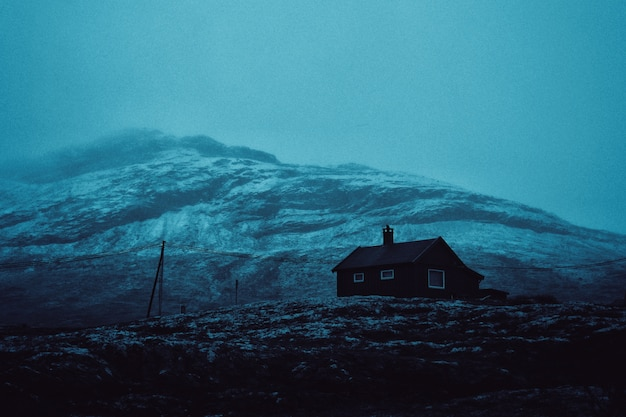 Mooie foto van een huis op een heuvel met een geweldige berg
