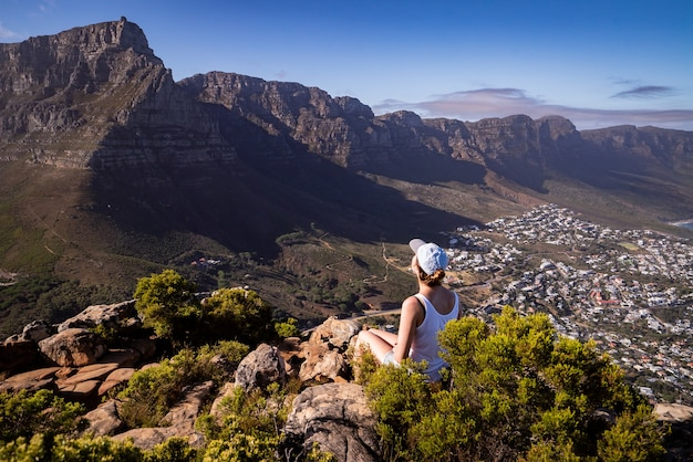 Mooie foto van een onherkenbare vrouw die op de rand van een klif zit en de stad kaapstad bewondert