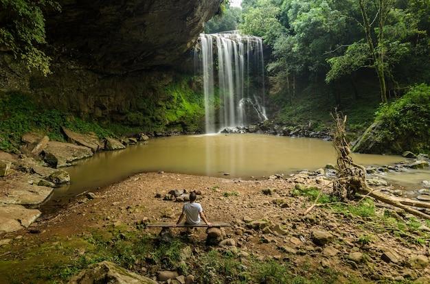 Mooie foto van een persoon die op een bankje zit en naar een prachtige waterval kijkt