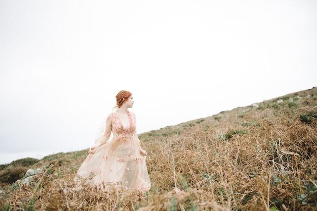 Mooie foto van een roodharig vrouwtje met een puur witte huid in een lichtroze jurk