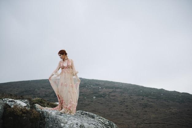 Mooie foto van een roodharig vrouwtje met een puur witte huid in een mooie lichtroze jurk