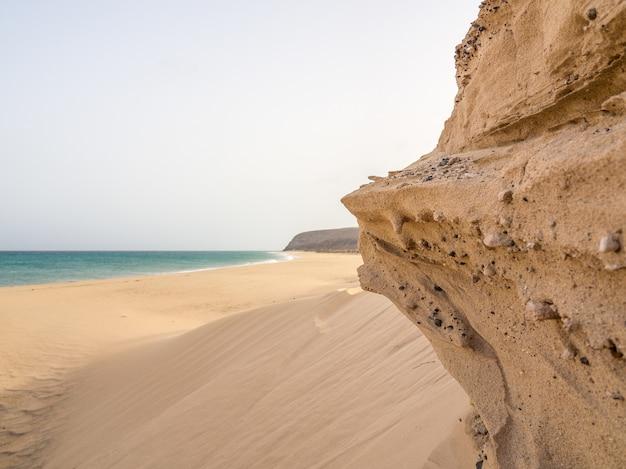Mooie foto van een rotsachtige zeekust met zacht zand en blauwe zee in fuerte ventura, canarische eilanden