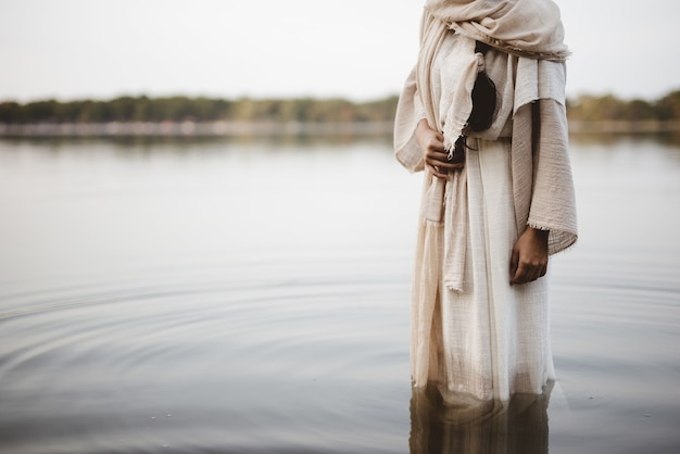Mooie foto van een vrouw die een bijbels gewaad draagt terwijl ze in het water staat