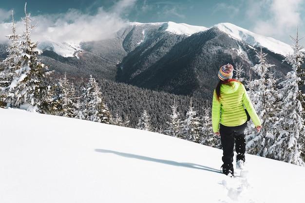 Mooie foto van een vrouw die in de winter op een helling loopt met uitzicht op een bos