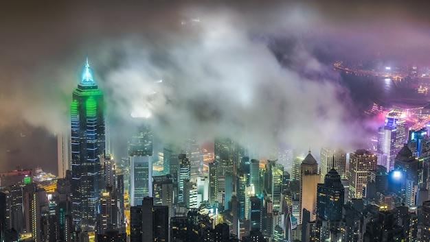 Mooie foto van hoge stadsgebouwen onder een bewolkte hemel 's nachts