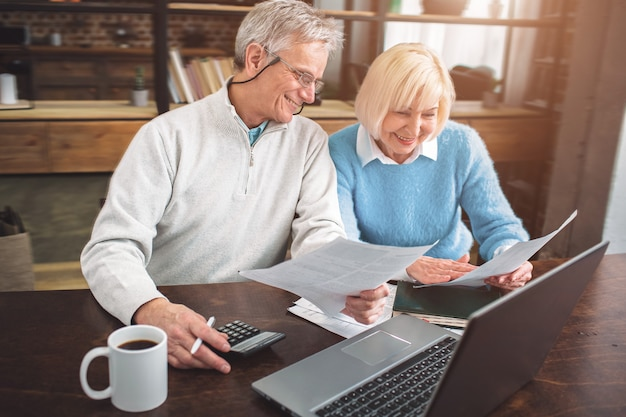 Mooie foto van senior man en vrouw die papieren bestuderen aan de tabl