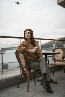 Mooie franse jonge vrouw zittend op het terras van het restaurant met koffiemok kijken camera portret o...