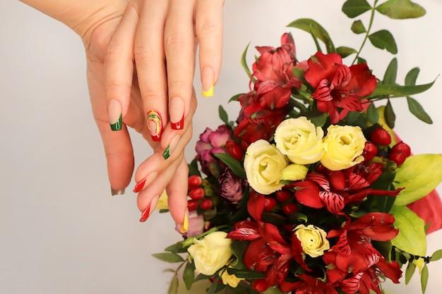 Mooie franse manicure aan de hand van een vrouw met bloemen.