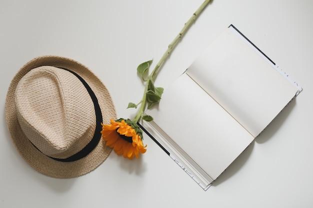 Mooie frisse gele zonnebloem, strohoed en een boek op een tafelblad uitzicht