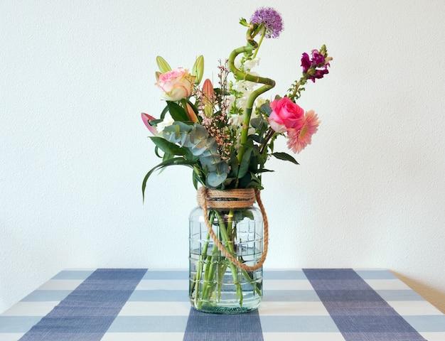 Mooie frisse heldere en kleurrijke lentebloemen in een helder boeket van glasvaas