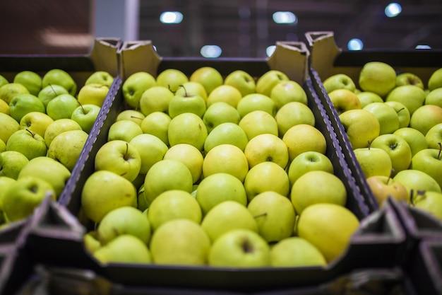 Mooie fruitachtergrond met groene en gele appels in een kartonnen doos.