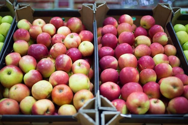 Mooie fruitachtergrond met rode appels in een kartonnen doos.