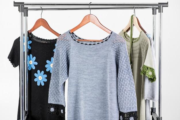Mooie gebreide jurken die op een hanger op een lichte achtergrond hangen
