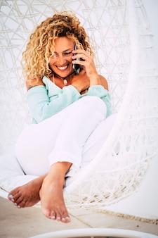 Mooie gebruinde dame gaat zitten op een witte coach-outdor op een goede plek om een telefoongesprek te voeren met vrienden