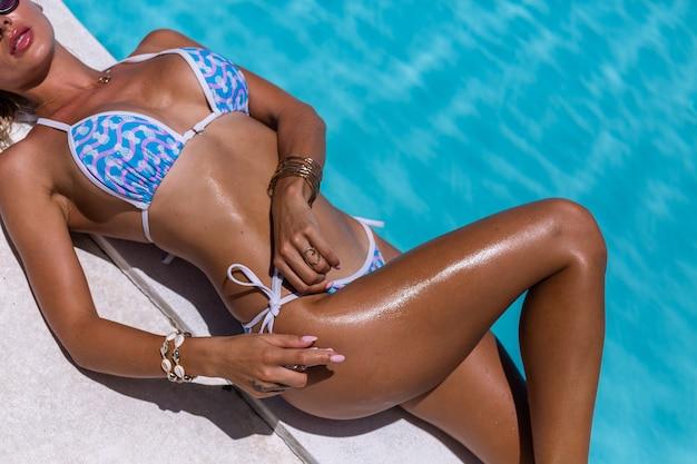Mooie gebruinde fit blanke vrouw brons glanzende huid in bikini met kokosolie door blauwe zwembad zonnige dag