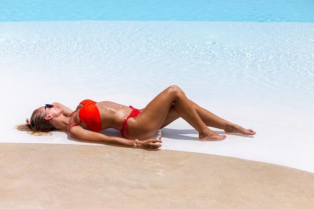 Mooie gebruinde fit blanke vrouw brons glanzende huid in bikini met kokosolie