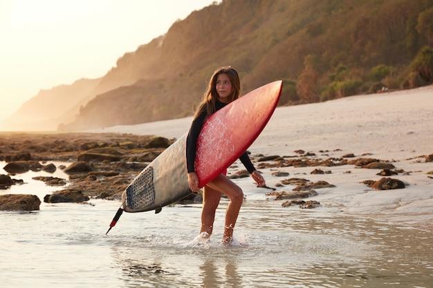 Mooie gebruinde jonge blanke vrouw draagt surfplank, heeft een wandeling over het water in de buurt van zandstrand