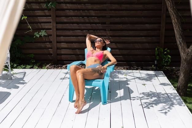 Mooie gebruinde slanke vrouw in bikini in achtertuin poseren op stoel