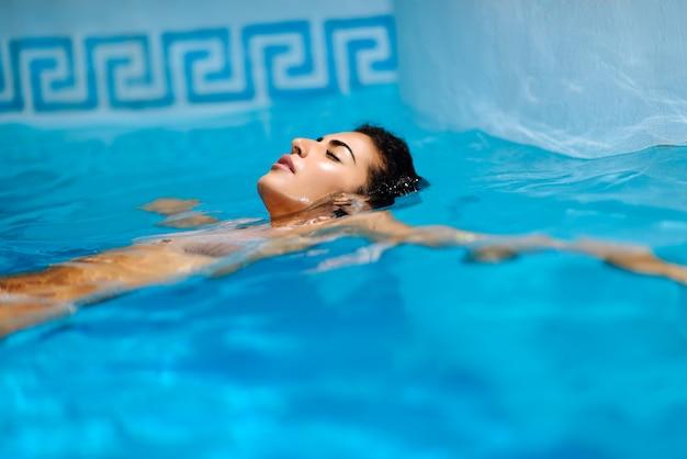 Mooie gebruinde vrouw in bikini ontspannen in het zwembad