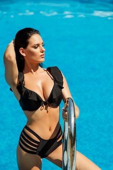 Mooie gebruinde vrouw met lang haar in zwarte bikini. vrouwen zomer mode.