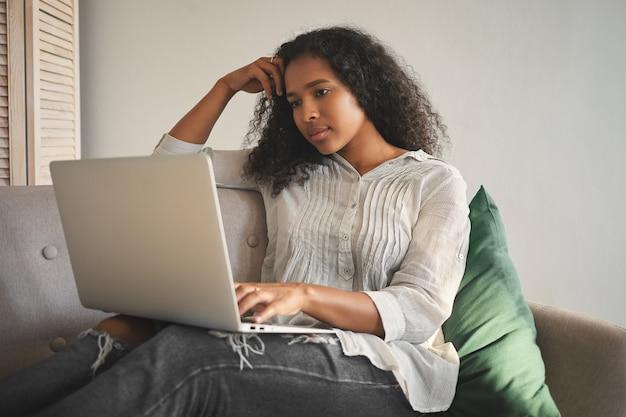 Mooie geconcentreerde jonge donkere vrouw met afro-kapsel studeert op afstand via online cursussen, met behulp van wifi op haar laptop terwijl ze thuis op de bank zit. mensen, technologie en onderwijs