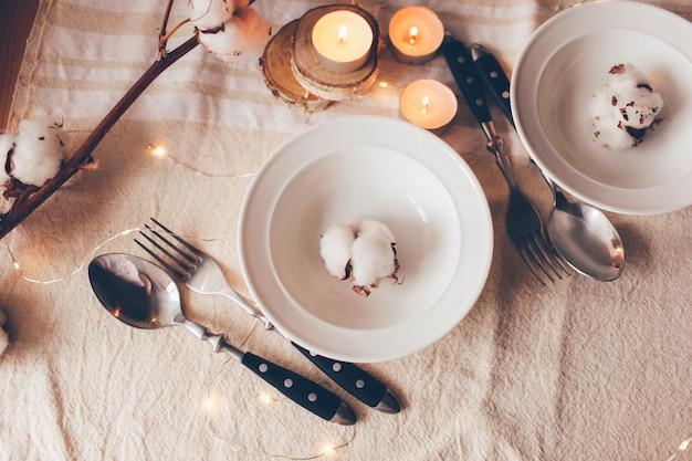 Mooie gedekte tafel met decoraties, kaarsen en katoenen tak op linnen tafelkleedtafel geserveerd voor de voorjaarslunch in de woonkamer. close-up, tabel instelling. lente decoraties.