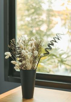 Mooie gedroogde bloemboeket in zwarte vaas met glazen venster achtergrond, slaapkamer interieur