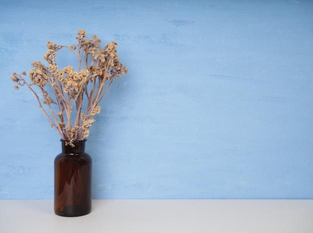 Mooie gedroogde bloemen in glazen vaas op een witte houten tafel met blauwe muurachtergrond met kopieerruimte, stilleven met zachte toon