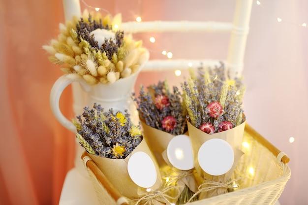 Mooie gedroogde bloemen in papier vakken met lichten op de achtergrond