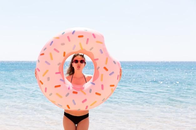 Mooie gekke vrouw ontspannen en spelen met opblaasbare ring in zee strand. zomervakantie en vakantie concept.