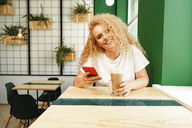 Mooie gekrulde blonde vrouw selfie te nemen zittend aan tafel in de coffeeshop