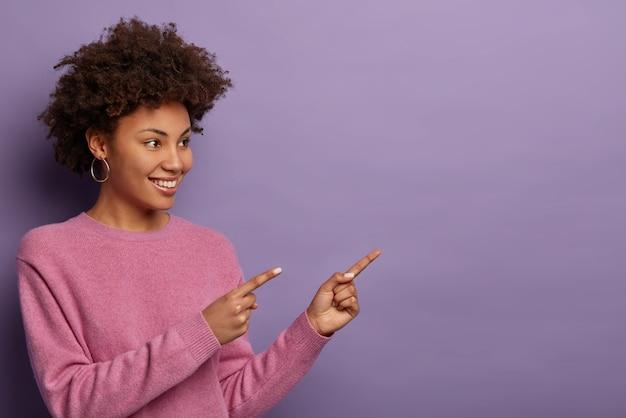 Mooie gekrulde etnische vrouw wijst naar kopie ruimte, suggereert klik op link of volg pagina om de nodige informatie te vinden, toont promo, reageert op geweldig nieuws, deelt fantastische advertenties.